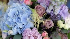 Disposition de différentes fleurs de différentes couleurs, se tenant sur des tables pour une décoration de vacances banque de vidéos