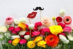 disposition de fleurs, fausses lèvres de papier et moustache dans des bâtons Photographie stock libre de droits