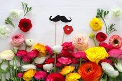 disposition de fleurs, fausses lèvres de papier et moustache dans des bâtons Image stock