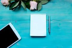 Disposition de fond de ressort sur un fond en bois bleu avec des fleurs des roses bloc-notes et feuilles pour des disques de styl Images libres de droits