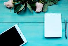 Disposition de fond de ressort sur un fond en bois bleu avec des fleurs des roses bloc-notes et feuilles pour des disques de styl Image libre de droits