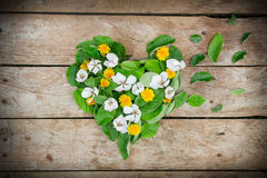 Disposition de forme de coeur faite de feuilles et fleurs sur la table Photographie stock libre de droits