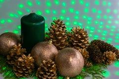 Disposition de Noël avec une bougie et des cônes de pin sur la verdure images stock