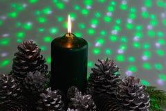 Disposition de Noël avec une bougie et des cônes de pin sur la verdure image stock