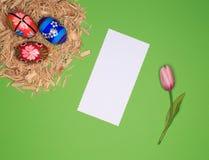 Disposition de Pâques avec le panier de Pâques, bois, oeufs, livre blanc, fleur Images libres de droits