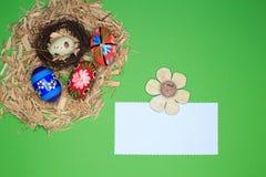 Disposition de Pâques avec le panier de Pâques, bois, oeufs, livre blanc, fleur en bois Image libre de droits