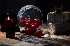 Disposition de verre à vin avec des raisins sur la table en bois avec du fromage bleu et la bouteille de vin rouge dans l'obscur images stock