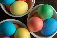 Disposition des oeufs de pâques brillamment colorés dans des trois cuvettes blanches images stock