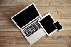 Dispositivi con gli schermi in bianco su fondo di legno fotografie stock libere da diritti