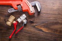 Dispositivi degli idraulici e della chiave inglese sull'annata Fotografia Stock Libera da Diritti