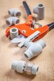 Dispositivi degli idraulici e taglierina di tubo sul bordo di legno Fotografia Stock