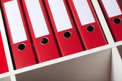 Dispositivi di piegatura di archivio rossi sulla cremagliera fotografia stock