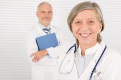 Dispositivi di piegatura sorridenti della stretta degli anziani della squadra del medico Fotografia Stock