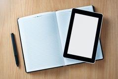 Dispositivo da tabuleta acima do caderno com a pena na tabela Foto de Stock