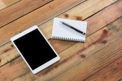 Dispositivo da tabuleta na tabela de madeira do espaço de trabalho Foto de Stock Royalty Free