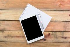 Dispositivo da tabuleta na tabela de madeira do espaço de trabalho Fotos de Stock Royalty Free