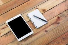 Dispositivo da tabuleta na tabela de madeira do espaço de trabalho Imagens de Stock