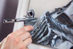 Dispositivo de acero del aerógrafo del cromo en la mano humana, pintando con el aerógrafo, opinión del primer Imagen de archivo libre de regalías