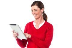 Dispositivo de almohadilla táctil de funcionamiento sonriente de la mujer Imagen de archivo libre de regalías