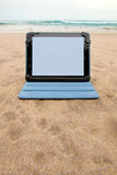 Dispositivo de la tableta en la playa Fotos de archivo