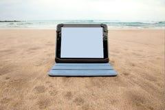 Dispositivo de la tableta en la playa Fotos de archivo libres de regalías