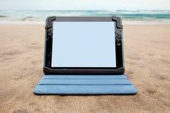 Dispositivo de la tableta en la playa Imágenes de archivo libres de regalías