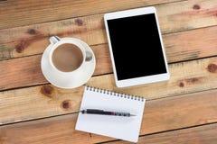 Dispositivo de la tableta en la tabla de madera del espacio de trabajo Foto de archivo libre de regalías