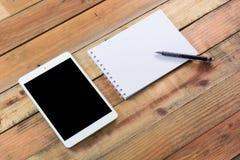 Dispositivo de la tableta en la tabla de madera del espacio de trabajo Foto de archivo