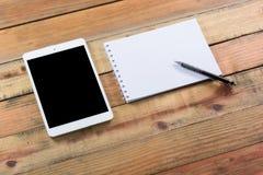 Dispositivo de la tableta en la tabla de madera del espacio de trabajo Imágenes de archivo libres de regalías