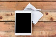 Dispositivo de la tableta en la tabla de madera del espacio de trabajo Fotografía de archivo libre de regalías