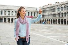 Dispositivo de terra arrendada feliz da mulher que toma uma foto quando em marcas do St Fotos de Stock