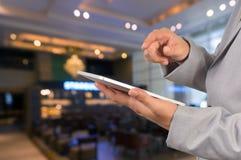 Dispositivo de Use Wireless Tablet del hombre de negocios en restaurante con Bokeh Imagenes de archivo