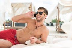 Dispositivo de utilização masculino farpado novo alegre na praia Fotos de Stock Royalty Free