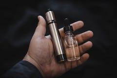 Dispositivo de Vaping dentro na mão do ` s do homem Cigarro eletrônico, vape Imagens de Stock