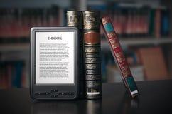 Dispositivo del lettore del libro elettronico sullo scrittorio in biblioteca immagini stock