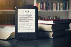 Dispositivo del lettore del libro elettronico sullo scrittorio in biblioteca fotografia stock