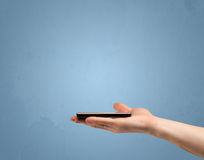 Dispositivo del telefono della tenuta dal profilo Fotografia Stock Libera da Diritti