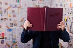 Dispositivo di piegatura top-secret Ottenere informazioni Cartella della lettura, cartella sulla sedia fotografia stock
