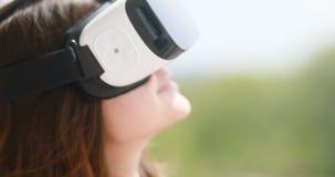 Dispositivo digital de los vidrios de la realidad virtual del desgaste de mujer joven, vídeo hermoso sonriente feliz del entreten almacen de metraje de vídeo