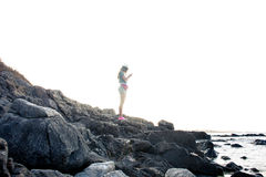 Dispositivo digital do uso do caminhante da mulher na costa rochosa no por do sol, isolado Imagens de Stock Royalty Free
