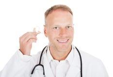 Dispositivo do doutor Holding Hearing Aid imagens de stock royalty free