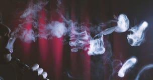 Dispositivo electrónico del cigarrillo de Vaping o cig de e de un hombre joven Fotografía de archivo