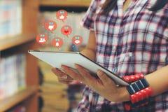 Dispositivo elegante de la tableta de la tenencia de la mano de la mujer con el holograma o el icono de la tecnología de comunica imágenes de archivo libres de regalías