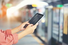 Dispositivo elegante de la tableta de la tenencia de la mano de la mujer en el tren de cielo del BTS en el fondo de Bangkok, Tail imagenes de archivo