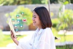 Dispositivo elegante del inconformista de la muchacha de la mano de la tableta feliz de la tenencia con hologra fotografía de archivo