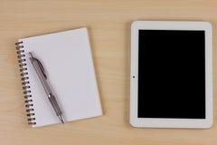 Dispositivo eletrónico com livro e pena na tabela de madeira Foto de Stock Royalty Free