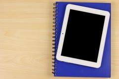 Dispositivo eletrónico da tela vazia com o caderno na tabela de madeira Fotografia de Stock Royalty Free