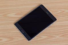Dispositivo eletrónico preto, PC da tabuleta na tabela de madeira Foto de Stock