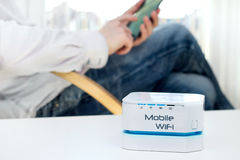 Dispositivo mobile del router di WiFi sulla tavola e sull'uomo d'affari Immagine Stock
