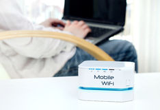 Dispositivo mobile del router di WiFi sulla tavola e sull'uomo d'affari Fotografia Stock